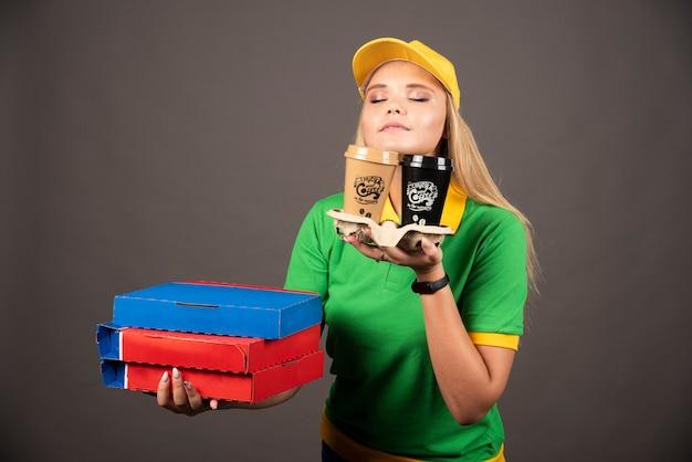 Repartidora sosteniendo tazas de café y cartones de pizza.