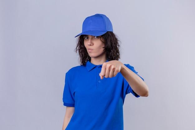 Repartidora en uniforme azul y gorra gesticulando puño como si saludara mirando con expresión sospechosa de pie en blanco aislado