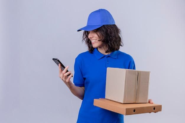 Repartidora en uniforme azul y gorra sosteniendo cajas de pizza y paquete de caja mirando la pantalla del teléfono móvil sonriendo con cara feliz de pie en blanco