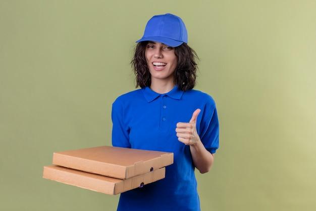 Repartidora en uniforme azul y gorra sosteniendo cajas de pizza y sonriendo alegremente mostrando los pulgares para arriba en verde aislado