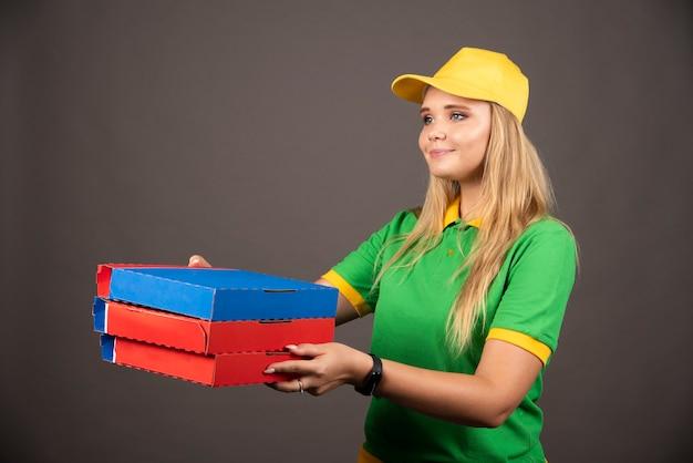Repartidora en uniforme dando cartones de pizza.