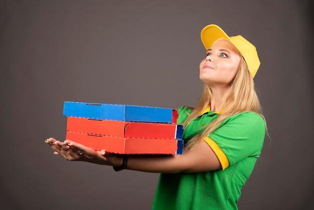 Repartidora en uniforme sosteniendo cartones de pizza. foto de alta calidad