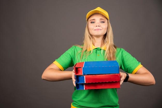 Repartidora en uniforme sosteniendo cartones de pizza.