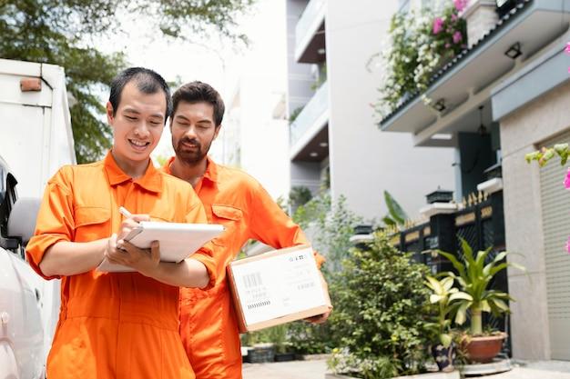 Repartidores jóvenes comprobar la información para la entrega
