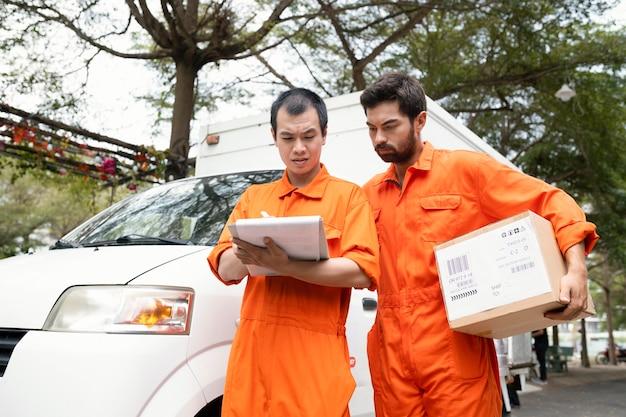 Repartidores jóvenes que controlan la información para la entrega cerca del coche