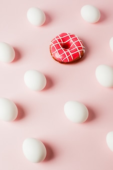 Repetición de huevos blancos de pascua con sombra y rosquilla sobre fondo rosa pastel