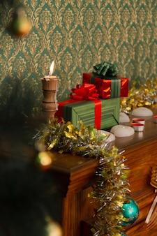 Repisa de chimenea con regalos en embalaje rojo, decorada para navidad con oropel y velas