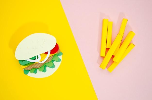 Réplicas de hamburguesas y papas fritas sobre fondo de color