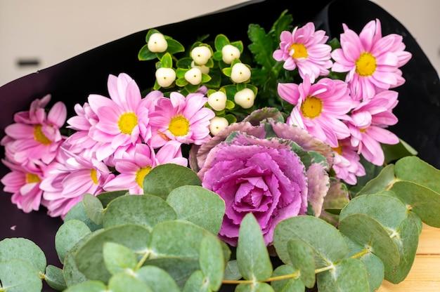 Repollo ornamental con crisantemos y otras hierbas
