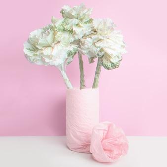 Repollo ornamental en un jarrón, envuelto con papel rosa sobre pared rosa