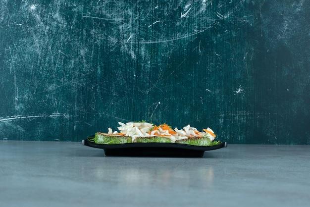 Repollo picado y zanahorias con pimiento asado sobre placa negra.