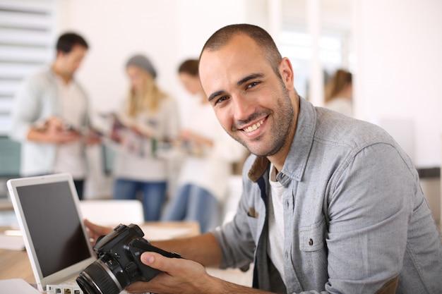 Reportero alegre que trabaja en la oficina en la computadora portátil