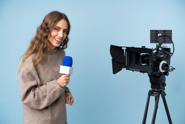 Reportero joven sosteniendo un micrófono y reportando noticias