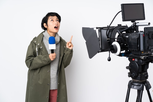 Reportero vietnamita mujer sosteniendo un micrófono y reportando noticias apuntando hacia arriba y sorprendido