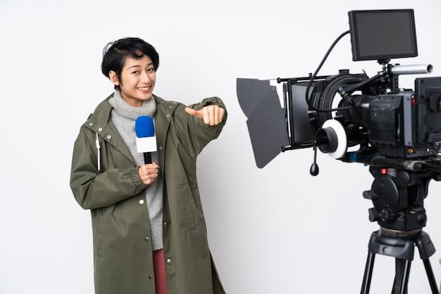 Reportero vietnamita mujer sosteniendo un micrófono y reportando noticias dando un gesto de aprobación