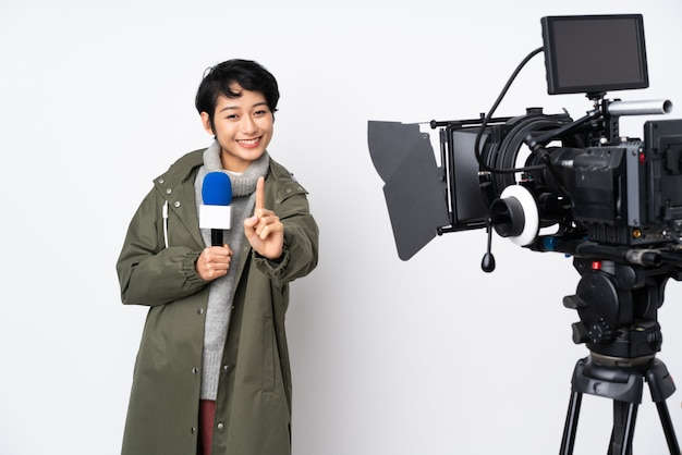 Reportero vietnamita mujer sosteniendo un micrófono y reportando noticias mostrando y levantando un dedo