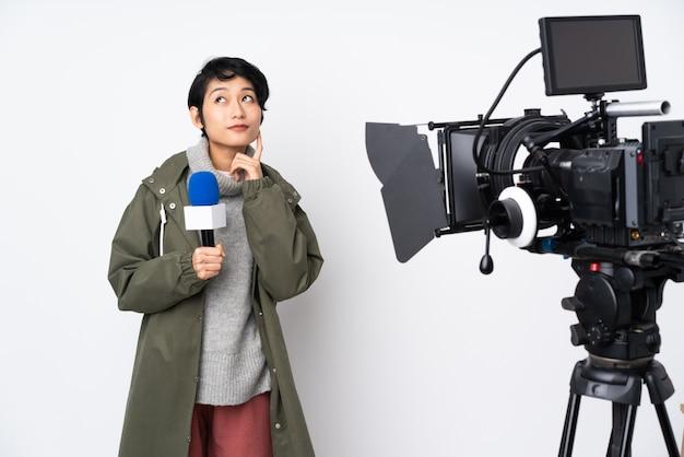 Reportero vietnamita mujer sosteniendo un micrófono y reportando noticias pensando en una idea mientras mira hacia arriba