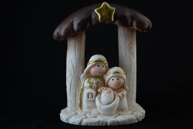 Representación de un belén navideño con las figuritas del niño jesús, maría y josé sobre fondo negro. concepto de navidad.