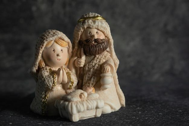 Representación de un belén navideño con las pequeñas figuras del niño jesús, maría y josé sobre un fondo de roca.