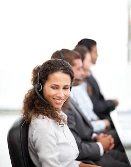 Representante feliz con sus colegas que trabajan en un centro de llamadas