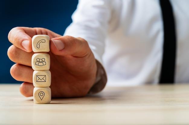 Representante de servicio al cliente apilando dados de madera con iconos de contacto e información.