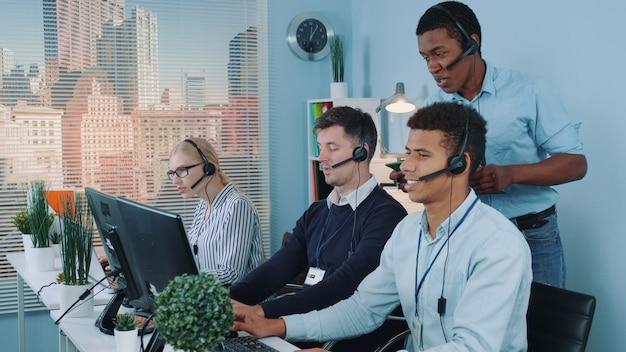Representante de servicio al cliente multiétnico que cuenta una broma a sus colegas mientras llama a los clientes