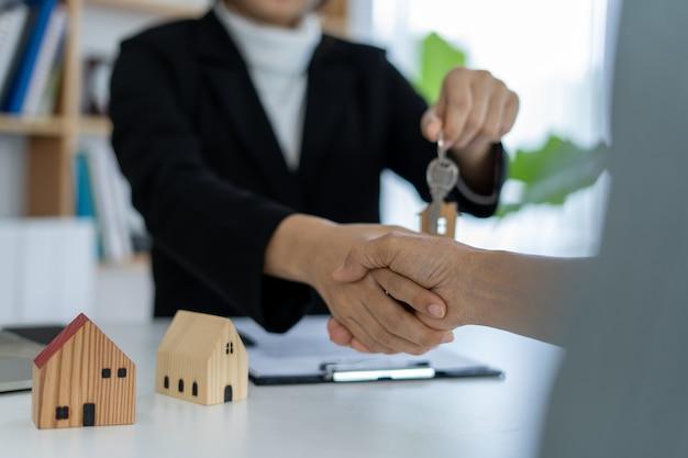 El representante de ventas se da la mano y entrega las llaves a los nuevos propietarios.