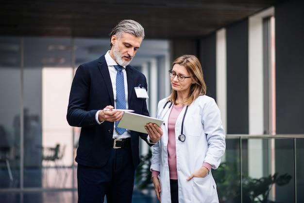 Representante de ventas farmacéuticas con tableta hablando con la doctora.