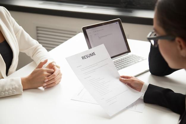 Representantes de la compañía que leen el curriculum vitae del solicitante en la contratación