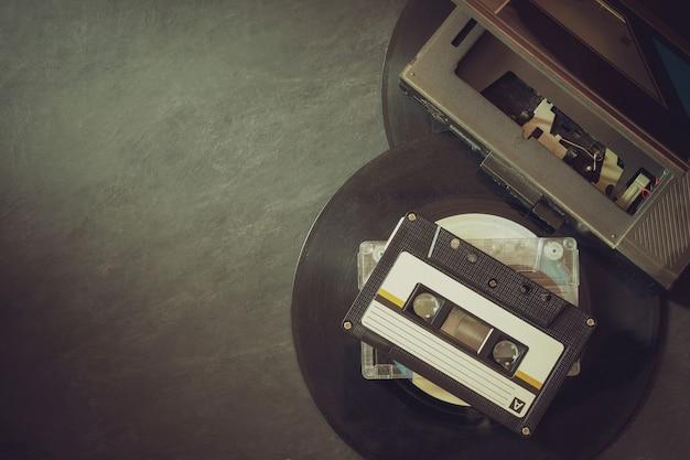 Reproductor de cassettes y disco en piso de cemento.