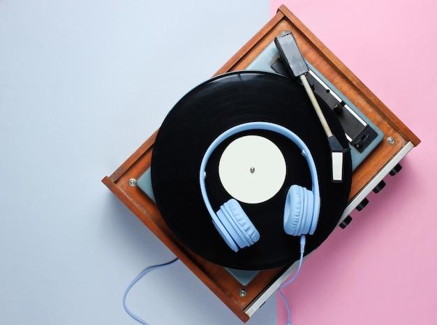 Reproductor de discos de vinilo retro, auriculares en el fondo pastel
