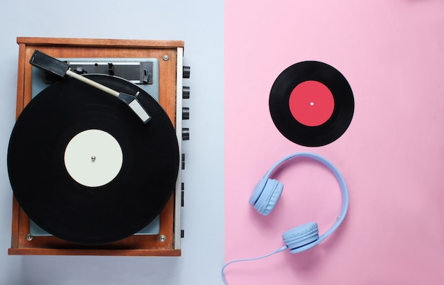 Reproductor de discos de vinilo retro, auriculares sobre fondo gris rosa