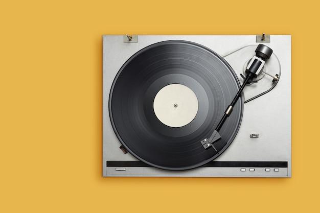 Reproductor de vinilo con larga duración o disco lp sobre fondo amarillo. vista superior, espacio de copia.