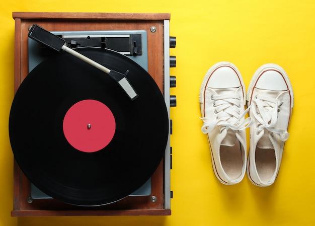 Reproductor de vinilo, zapatillas viejas sobre el fondo amarillo. estilo retro, cultura pop, años 80, vista superior