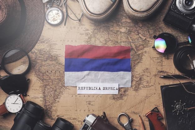 República srpska bandera entre los accesorios del viajero en el mapa antiguo de la vendimia. tiro de arriba