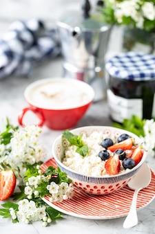 Requesón con bayas, mermelada, fresas frescas y una taza de café con crema para el desayuno.