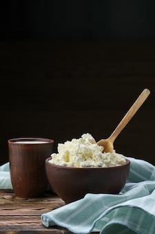Requesón con cuchara de madera y leche en loza sobre mesa de madera