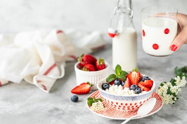 Requesón con fresas frescas y leche para el desayuno.