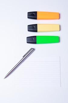Resaltadores de colores, bolígrafos, marcadores y papel en blanco para trabajar o estudiar