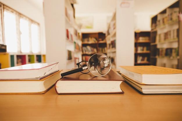 Reserve en la biblioteca con el viejo libro de texto abierto, apile pilas de archivos de texto de literatura en el escritorio de lectura