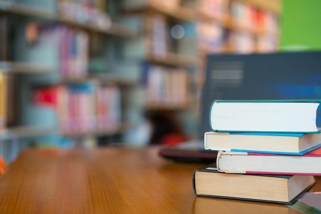 Reserve en la biblioteca con un viejo libro de texto abierto, apile pilas de archivos de texto de literatura en la mesa de lectura