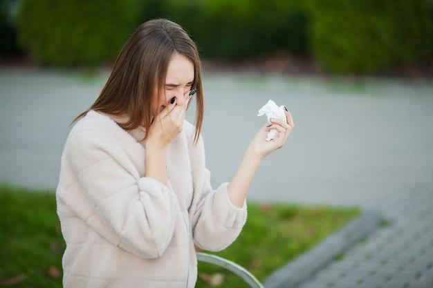 Resfriado y gripe. joven atractiva, resfriada en la calle, se limpia la nariz con una servilleta