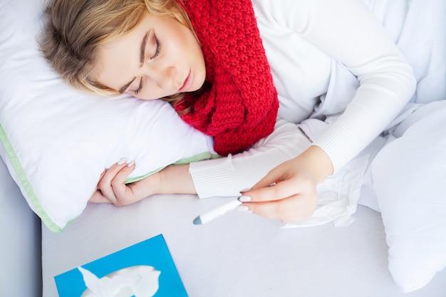 Resfriado y gripe, mujer enferma acostada en una cama con un termómetro