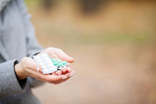 Resfriado y gripe. mujer en otoño parque con pastillas