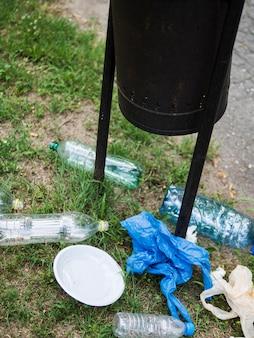 Residuos de basura plástica debajo del contenedor negro en el parque