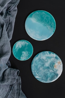 Resina epoxi turquesa sobre fondo negro placas redondas