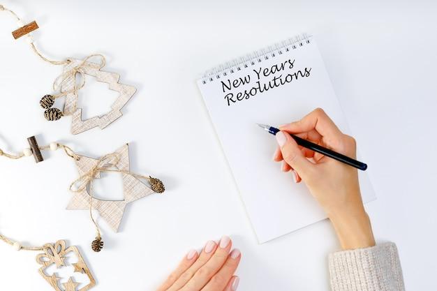 Resolución de año nuevo con una persona con una pluma y cuaderno. resoluciones, metas para el año nuevo.