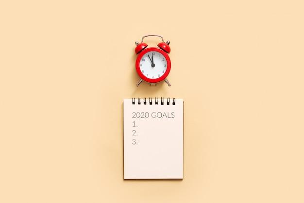 Resoluciones de año nuevo contra gastos generales del bloc de notas y reloj despertador.