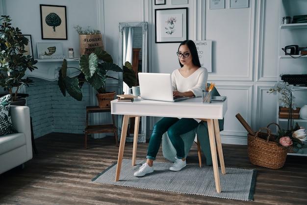 Resolviendo las cosas. hermosa joven trabajando con computadora mientras está sentado en la oficina en casa