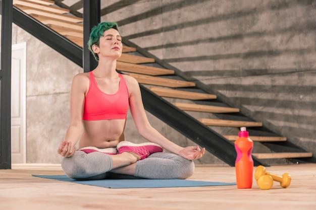 Respira y medita. mujer de pelo verde con top rosa respirando lentamente mientras medita en casa